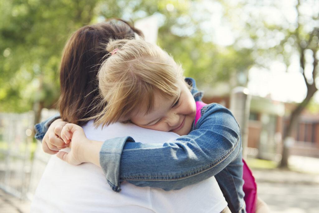 Mutter mit Kind (mit Prader-Willi-Syndrom) auf ihrem Arm